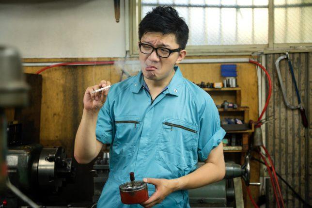 タバコを吸う作業服の男性